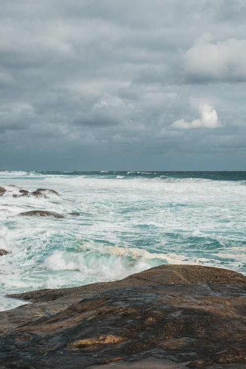Scenery of azure sea with foamy waves rolling on wet rough seacoast beneath dull cloudy sky