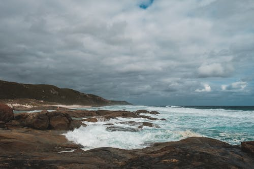 Dull sky over rough seacoast washed by stormy sea