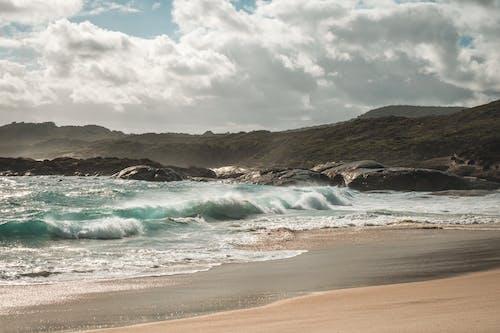 Scenery of azure foamy sea waving on sandy beach near rough grassy cliff on sunny day
