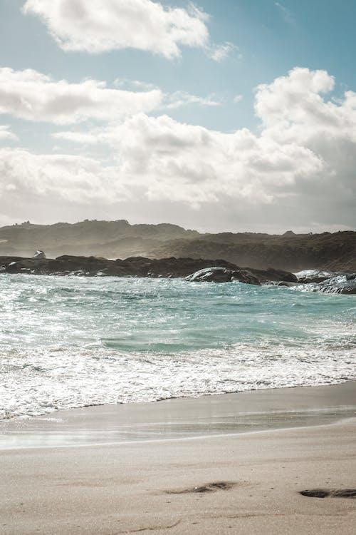 Rippling blue sea near sandy beach and hilly coast