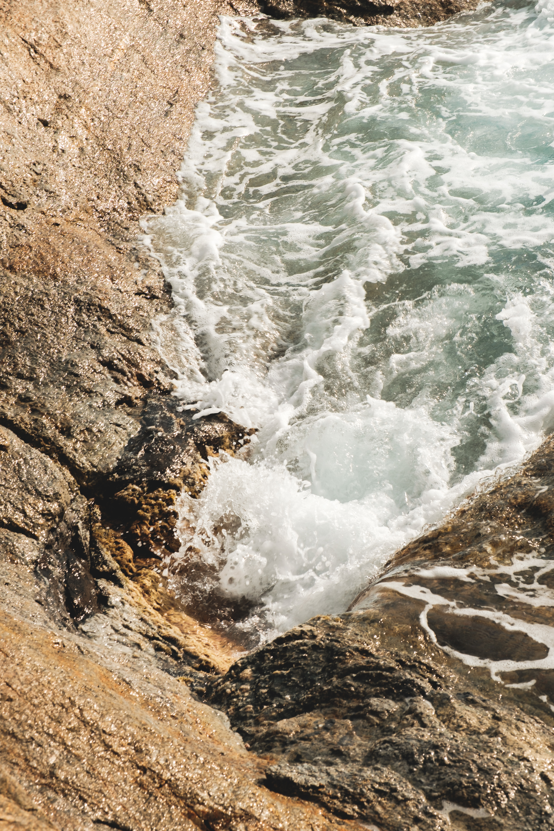 foamy seawater washing rough rocky cliff