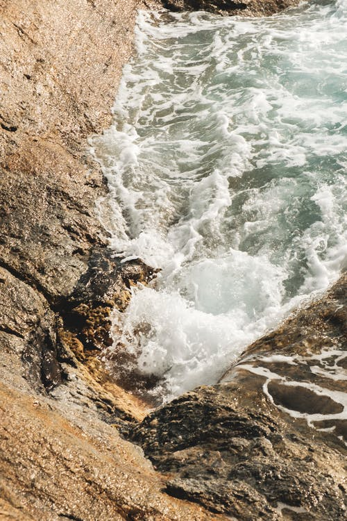 From above clean foamy seawater washing rough rocky cliff slopes on sunny day