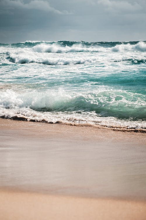Amazing view of stormy azure sea with foamy waves rolling on wet sandy beach on cloudy overcast day