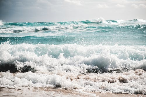 Turquoise stormy sea with foamy waves splashing on sandy beach against cloudy sky