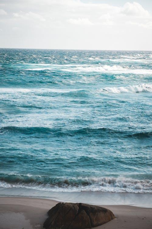 Foamy waves washing sandy beach with big stone