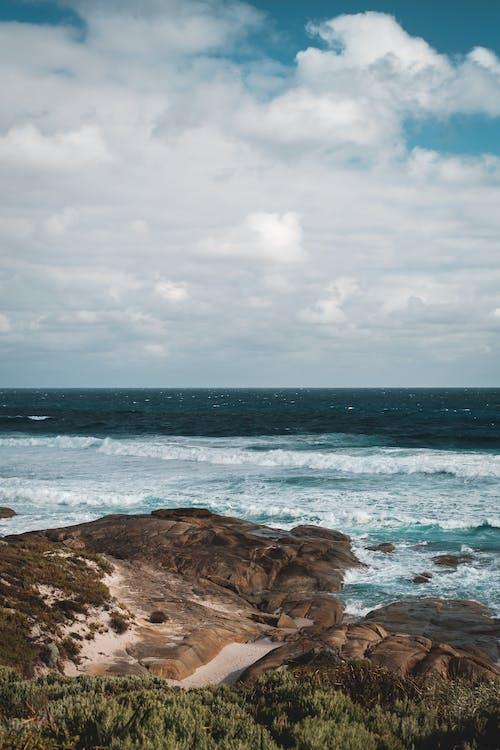 Rocky coast of foamy ocean under cloudy sky on sunny day