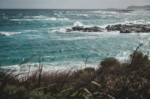 Breathtaking scenery of powerful ocean with turquoise water and foamy waves crashing on rocky formations near hill covered with dry grass on sunny day