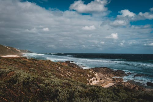 Majestic scenery of endless turquoise ocean with powerful foamy waves washing sandy coast and rough boulders near rocky mountain covered with green grass under cloudy blue sky