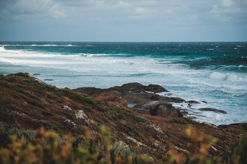 Stormy ocean washing rocky coast against cloudy sky