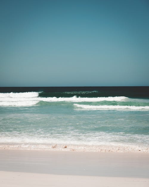 Picturesque wavy water of ocean washing sand of shore under cloudless blue sky