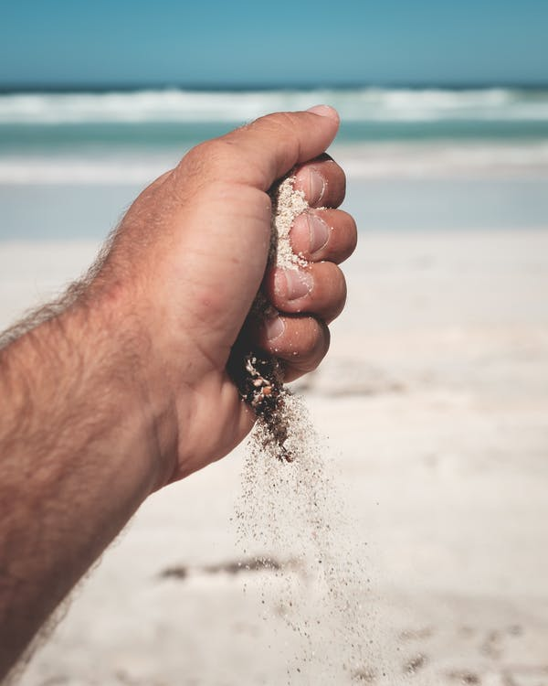 Crop anonymous male pouring sand on blurred background of wavy foamy ocean under blue sky