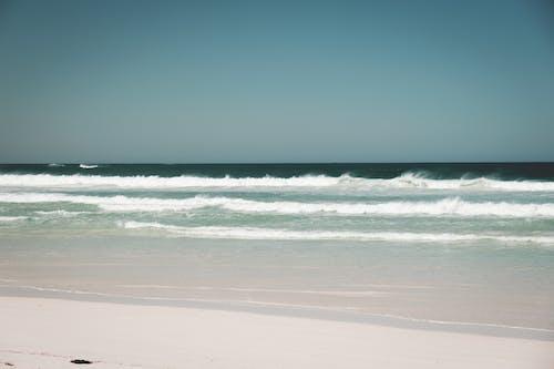 White sandy coast washed by foamy blue ocean