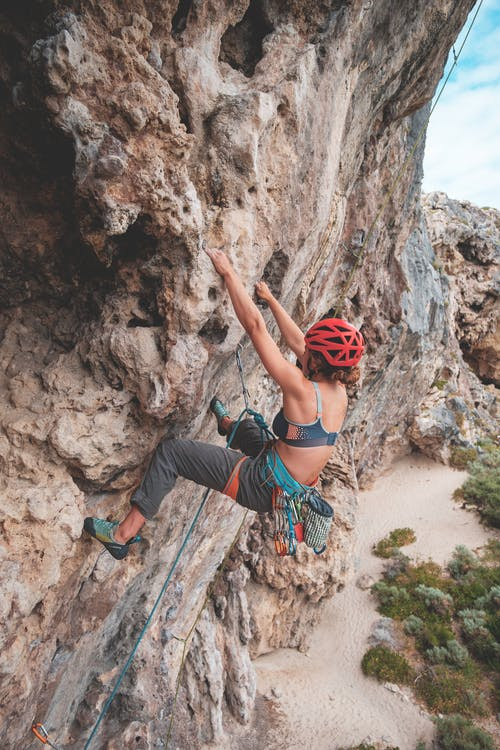 Side view of anonymous female with rope in helmet climbing on stony terrain