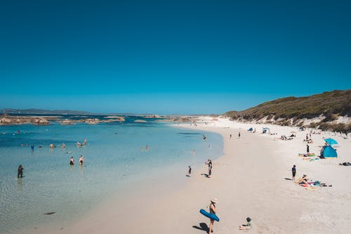 Many people relaxing on sandy beach of tranquil ocean under cloudless bright blue sky