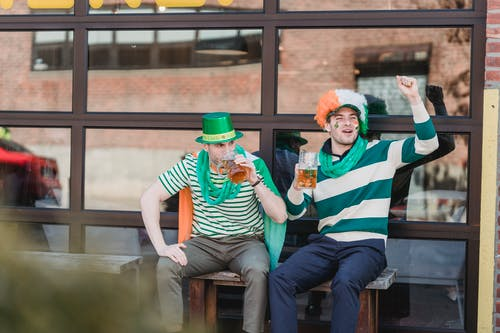Joyful men drinking beer and yelling on street during national festival party