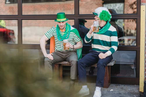 Happy young male friends in festive outfits drinking beer and communicating while relaxing on street bench during celebration of St Patricks Day