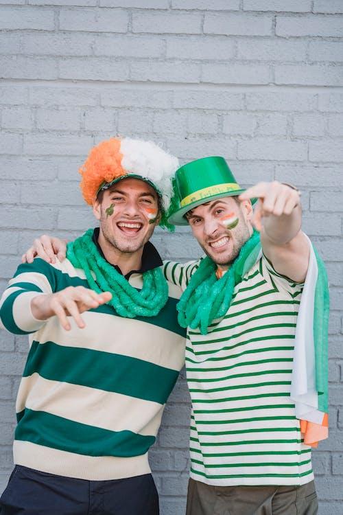 Smiling men celebrating Saint Patricks day on street