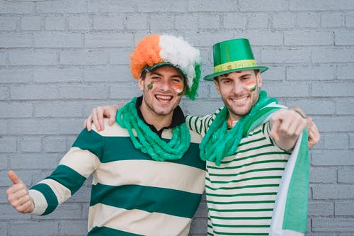 Delighted male friends in traditional colorful hats and flags of Ireland painted on faces looking at camera during holiday on street
