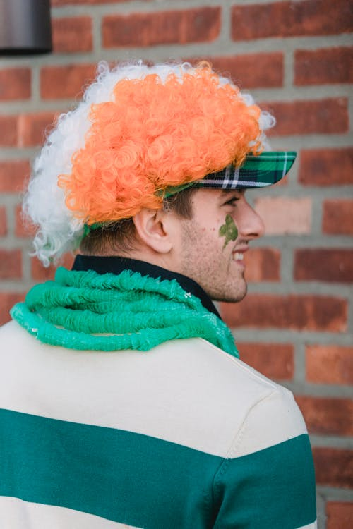 Side view of delighted male with painted shamrock on face wearing traditional outfit standing on street while celebrating holiday on street
