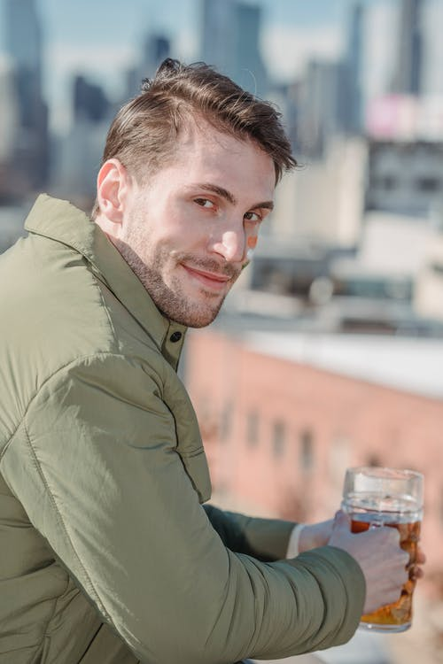 Happy man with beer on rooftop
