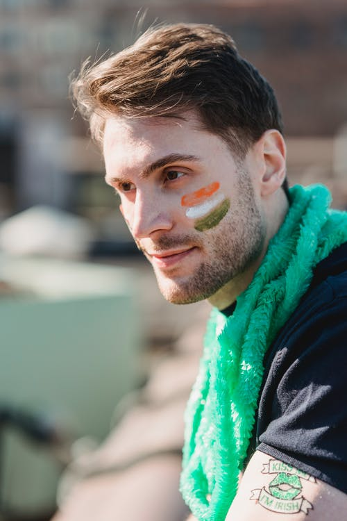 Pensive handsome male in casual outfit and green scarf with paint of Irish flag on cheek looking away on street