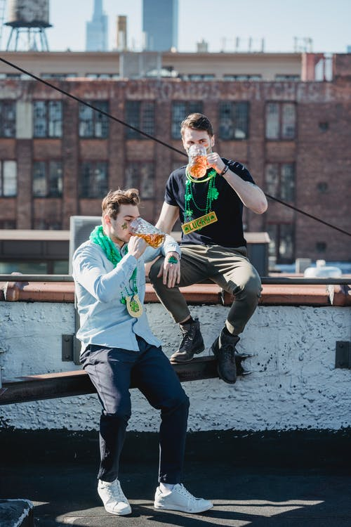 Full length of young trendy male millennials with festive accessories relaxing on rooftop of multistory building and drinking beer while celebrating Feast of Saint Patrick