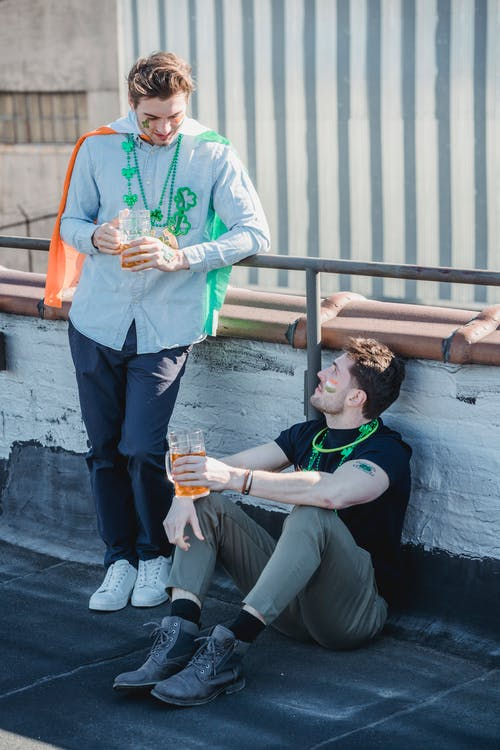 Full body of positive young guys in casual clothes and festive accessories chatting and drinking beer on rooftop during celebration of St Patricks Day
