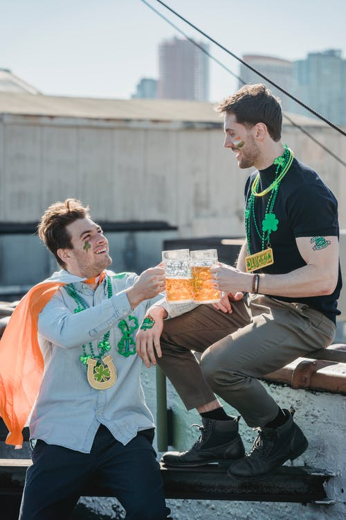 Cheerful young male friends clinking beer glasses during celebration of St Patricks Day