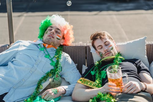 Football fans resting with mug of beer on terrace of bar