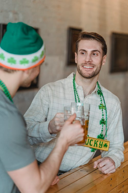 Happy young male raising mug of beer with friend sitting in pub and celebrating national holiday