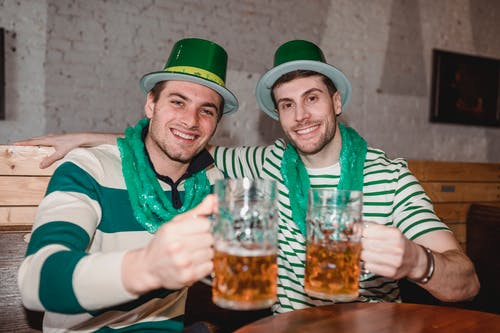 Cheerful young friends celebrating Saint Patrick day wearing national green hat and scarf raising mug of beer in pub