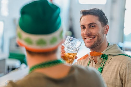 Cheerful man drinking beer and talking with friend