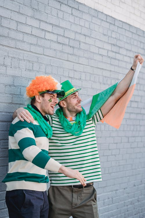 Side view of male friends wearing clown party wig and green stripe t shirt and green sparkle hat covered with irish flag greeting and celebrating Saint Patrick Day