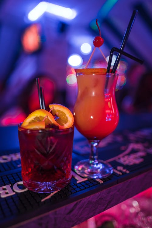 Sex on Beach and Negroni cocktails with garnishes in nightclub