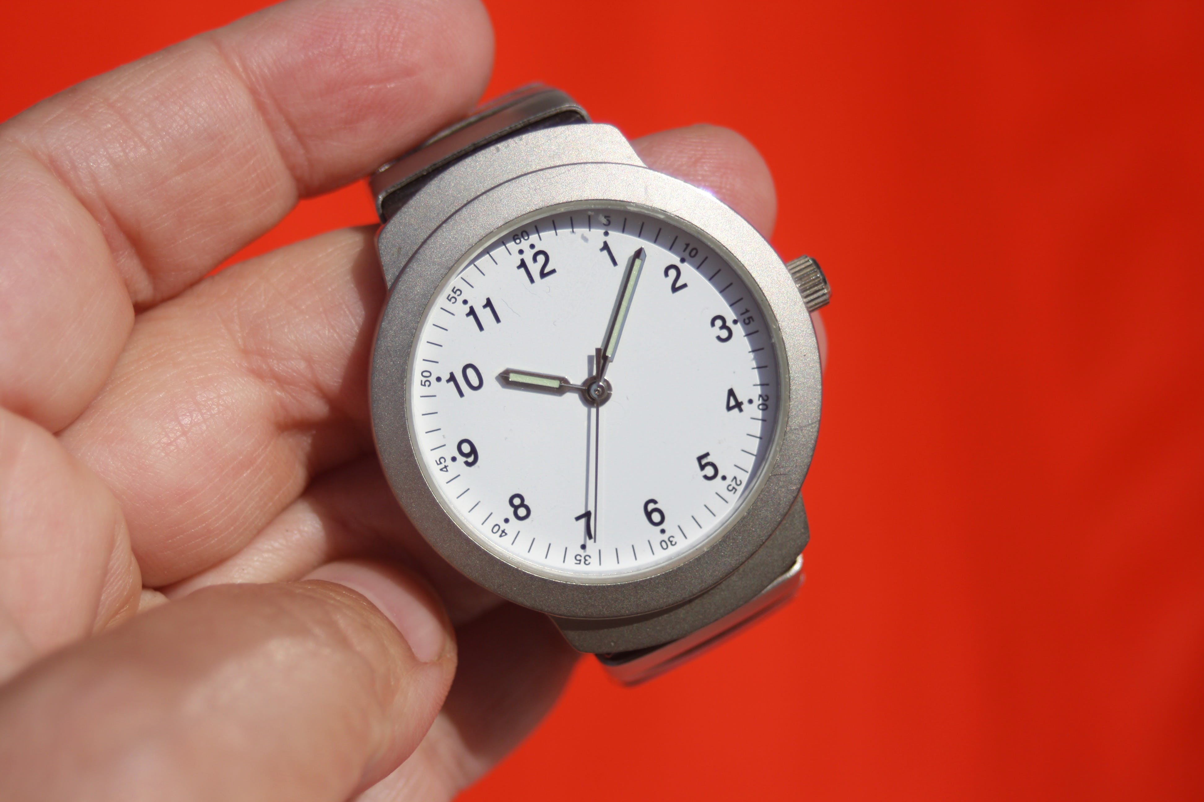 Person Holding Grey Round Analog Watch at 10:07