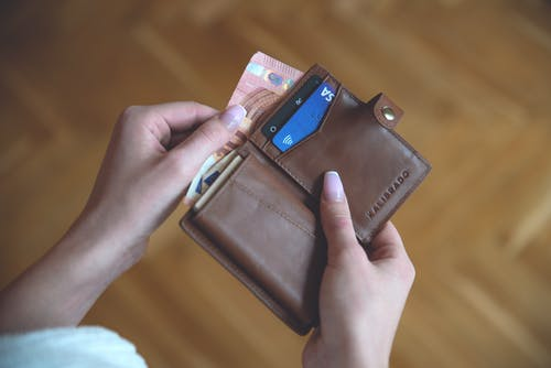 Close-Up Shot of a Person Holding a Brown Wallet