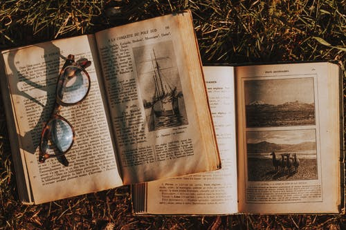 Top view paged of worn out textbooks with pictures and letters placed on grassy ground with eyeglasses in rural area