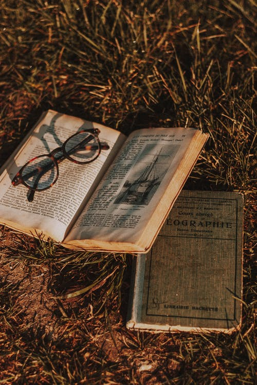 From above pages of worn out textbooks with text placed on grassy terrain with eyeglasses in rural area of countryside