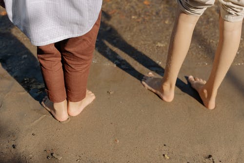 Close-Up Shot of Two People Standing on Beach