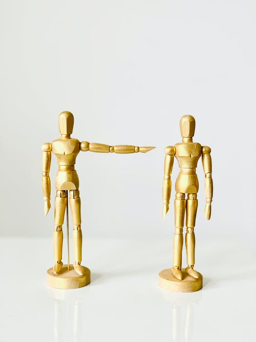 Close-Up Shot of a Golden Wooden Figurines on a Wooden Surface