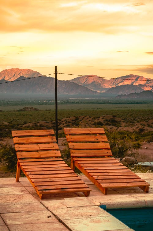 Brown Wooden Bench Near Green Grass Field and Mountains