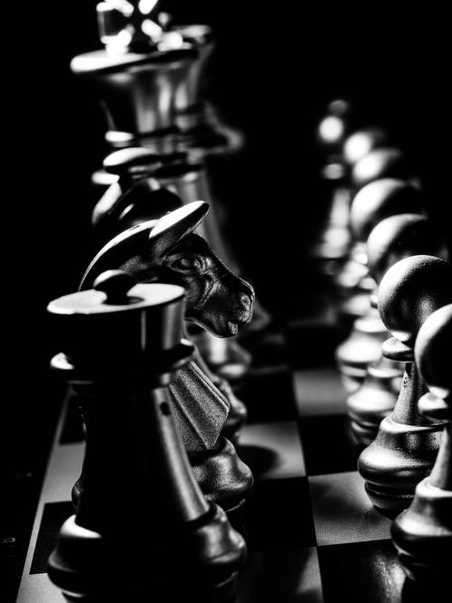 Grayscale Photo of Chess Pieces on a Chessboard