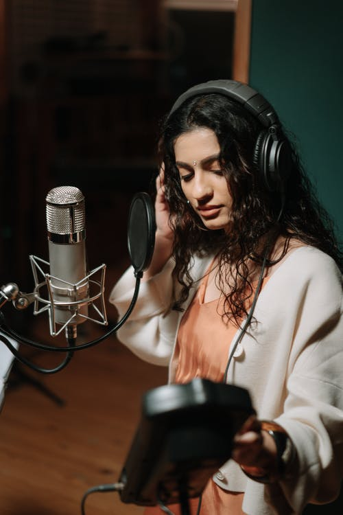 Woman in White Long Sleeve Shirt Sitting Beside Microphone