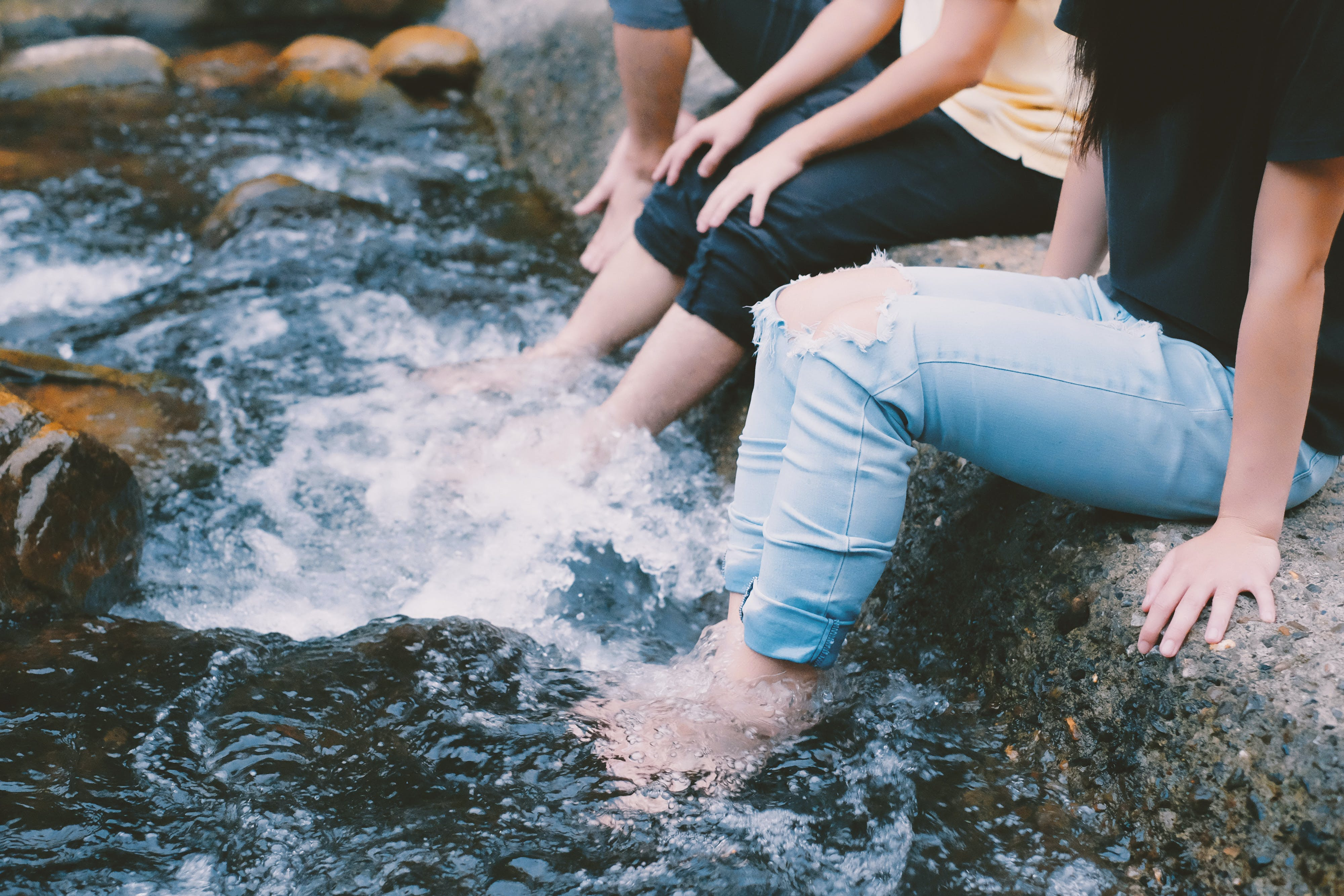 People In Jeans With Feet In Water