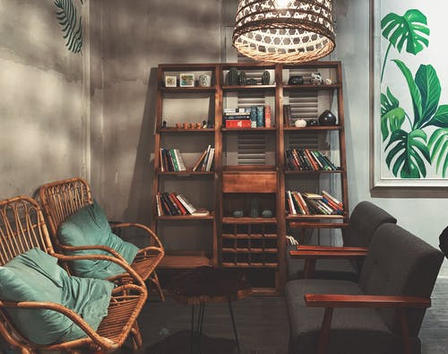 Brown Wooden Shelf With Books and Chairs