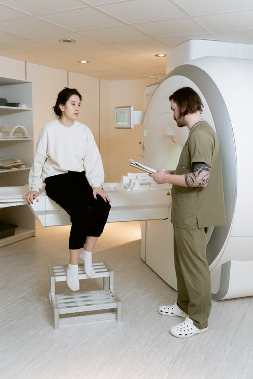 Photo Of Woman Sitting On A CT Scan Machine