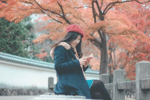 Woman in Blue Parka Jacket Sitting on Grey Concrete Bench Reading Book
