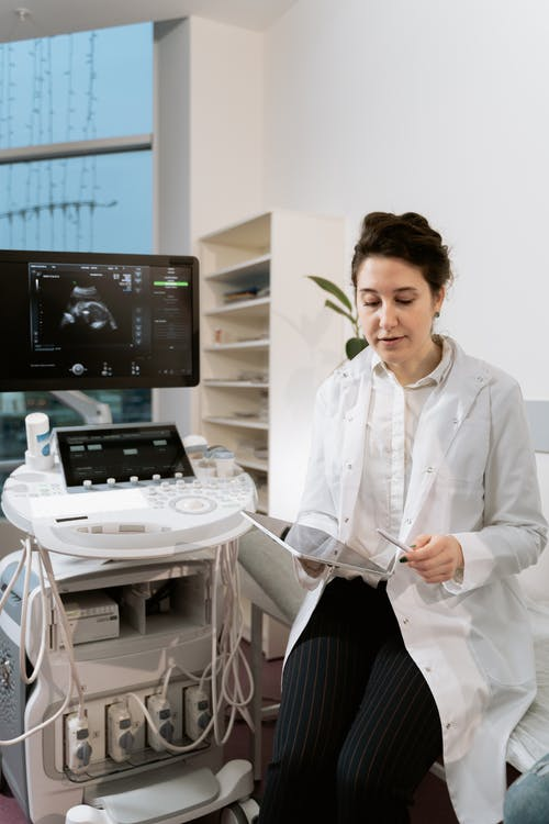 Photo Of An OB-GYN Sitting Beside Ultrasound Machine