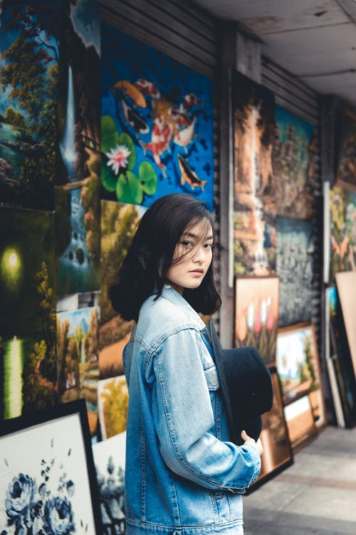 Side view of serious female in denim jacket standing against different painted pictures and looking at camera