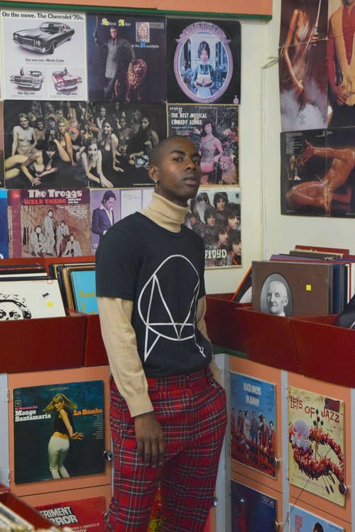 Trendy young African American male in checkered pants looking at camera against old books and vinyl records in music shop